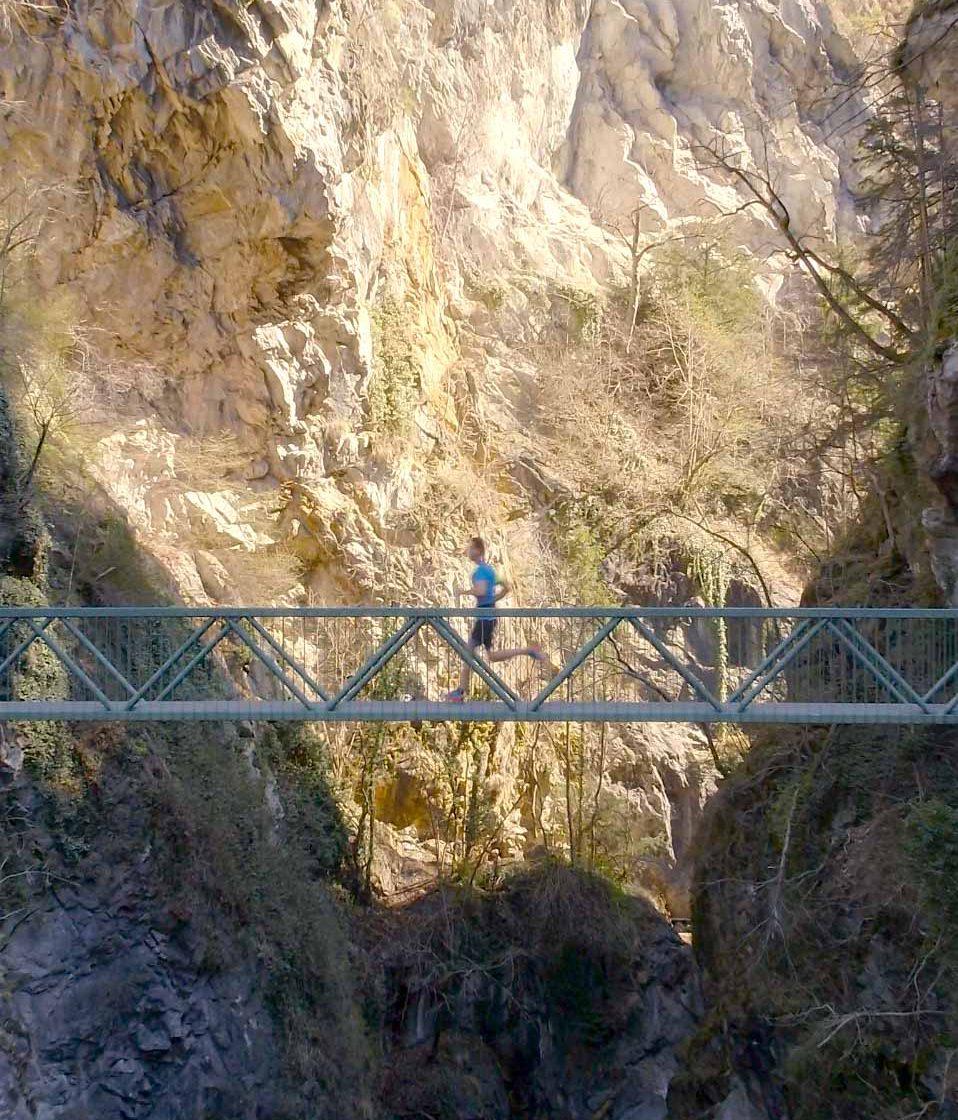 Vue par drone d'un coureur sur un pont en montagne
