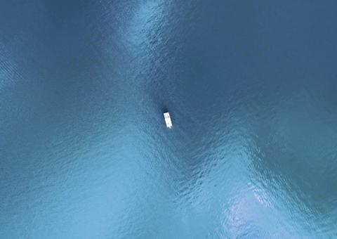 Bateau graphique au centre d'un lac vu par drone